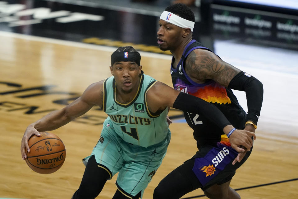 Charlotte Hornets guard Devonte' Graham drives to the basket past Phoenix Suns forward Torrey Craig during the first half of an NBA basketball game on Sunday, March 28, 2021, in Charlotte, N.C. (AP Photo/Chris Carlson)