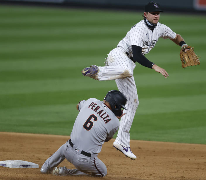FILE - Colorado Rockies second baseman Ryan McMahon, top, jumps over Arizona Diamondbacks' David Peralta after forcing him out at second base on a double play hit into by Christian Walker in the sixth inning of a baseball game in this file photograph taken Tuesday, Aug. 11, 2020, in Denver. McMahon is slated to return to his natural position, third base, with the trade of Nolan Arenado to St. Louis in the off-season. (AP Photo/David Zalubowski, File)