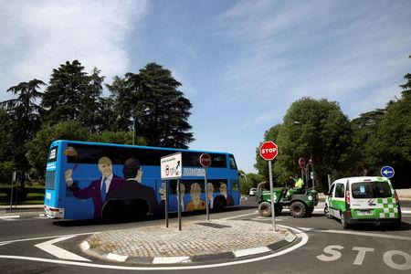 A municipal worker points at a bus sponsored by Podemos (We can) party painted with pictures representing Spain's recent political scandals as it tours Madrid, Spain April 18, 2017. Picture taken April 18, 2017. REUTERS/Susana Vera