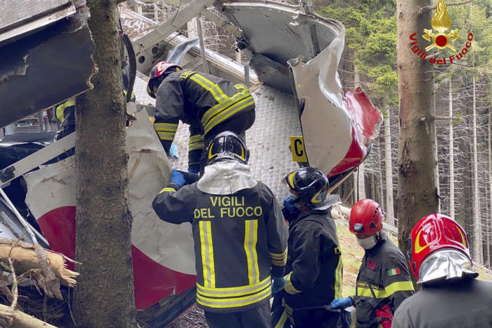 Rescuers work by the wreckage of a cable car after it collapsed near the summit of the Stresa-Mottarone line in the Piedmont region, northern Italy, Sunday, May 23, 2021. Italy's transport minister was heading Monday, May 24, 2021 to the scene of a cable car disaster that killed 14 people when the lead cable apparently snapped and the cabin careened back down the mountain until it pulled off the line and crashed to the ground. (Vigili del Fuoco Firefighters via AP)