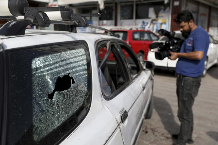 Afghan journalists films the vehicle in which director of Afghanistan's Government Information Media Center Dawa Khan Menapal was shot dead in Kabul, Afghanistan, Friday, Aug. 6, 2021. The Taliban shot and killed the director of Afghanistan's Government Information Media Center on Friday, the latest killing of a government official and one that comes just days after an assassination attempt on the acting defense minister. (AP Photo/Rahmat Gul)