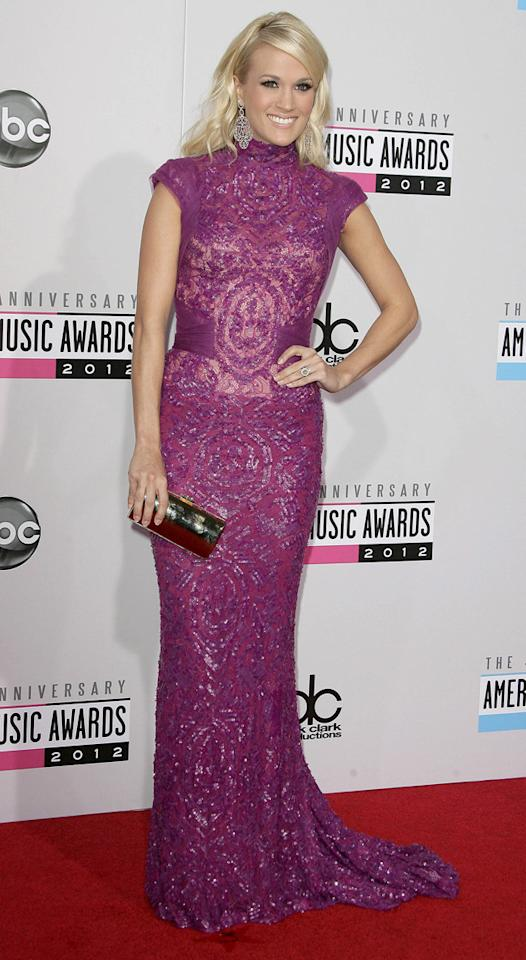 AMAs 2012: Carrie Underwood collected the award for best country album, and wore two outfits to celebrate. The first was this cap-sleeved full length purple dress with sequin embellishment and glamorous train. Copyright [WENN]