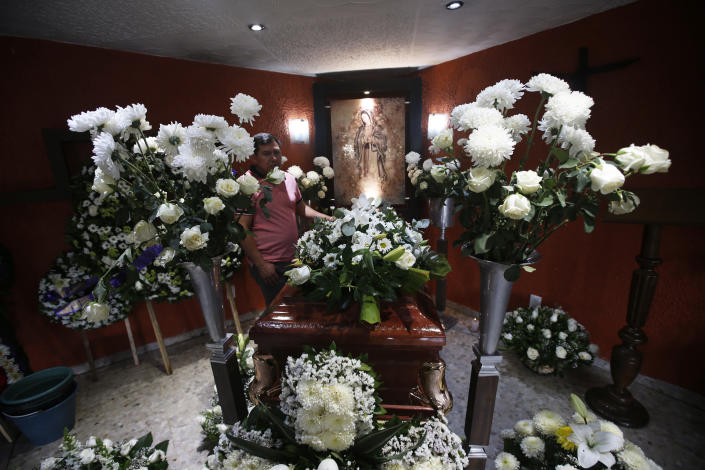 Funeral flowers surround the casket containing the remains of 37-year-old Liliana Lopez who died in the Mexico City Metro collapse disaster, during a wake in Mexico City, Wednesday, May 5, 2021. Monday night's accident was one of the deadliest in the history of the capital's subway system. (AP Photo/Marco Ugarte)