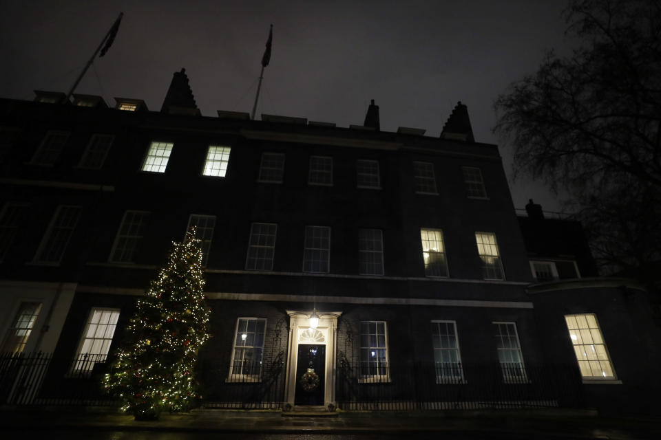 A view of the Christmas tree outside 10 Downing Street in London as people wait for news on Brexit trade talks, Wednesday, Dec. 23, 2020. European Union and British negotiators are closing in on a trade deal with only a disagreement over fishing remaining, After resolving a few remaining fair competition issues, negotiators were dealing with EU fisheries rights in U.K. waters Wednesday as they worked to secure a deal for a post-Brexit relationship after nine months of talks. (AP Photo/Kirsty Wigglesworth)