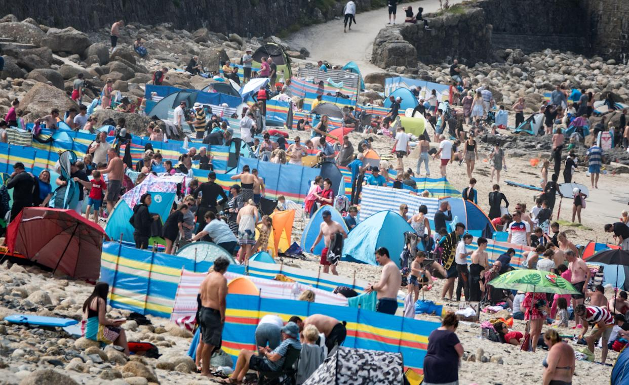 SENNEN COVE, ENGLAND - AUGUST 01: Crowds of people gather on the beach at Sennen Cove on August 1, 2021 in Cornwall, England. With international travel restrictions remaining likely for this summer at least, many parts of the UK are set to be very popular with holidaymakers opting to have domestic holiday or a so called staycation within the UK. (Photo by Matt Cardy/Getty Images)