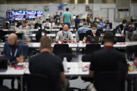 FILE - In this July 20, 2021, file photo, journalists work between plastic barriers in the main press center at the 2020 Summer Olympics, in Tokyo. (AP Photo/David Goldman, File)