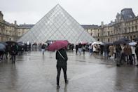 """A woman walks to the re-opened Louvre museum, a day after a man attacked French soldiers near the museum in Paris, Saturday, Feb. 4, 2017. The Louvre in Paris reopened to the public Saturday morning, less than 24-hours after a machete-wielding assailant shouting """"Allahu Akbar!"""" was shot by soldiers, in what officials described as a suspected terror attack. (AP Photo/Kamil Zihnioglu)"""