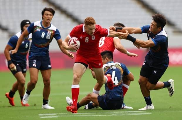 Canadian Connor Braid, left, scored a hat trick in the men's rugby sevens team's 36-12 win over Japan. (Siphiwe Sibeko/Reuters - image credit)