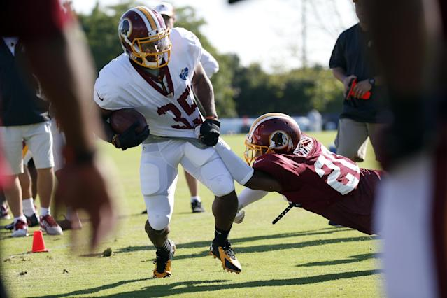 Washington Redskins running back Lache Seastrunk is brought down by cornerback Richard Crawford during practice at the team's NFL football training facility, Monday, July 28, 2014 in Richmond, Va. (AP Photo/Alex Brandon)