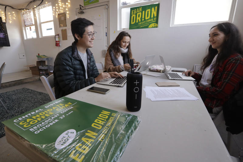 In this Wednesday, Oct. 23, 2019 photo, Seattle City Council candidate Egan Orion's staff members Harrison Louie, left, Olga Laskin and Akansha Bhat work at the campaign's headquarters in Seattle. Seven of the nine Seattle City Council seats are up for grabs in next month's election, where retail giant Amazon has made unprecedented donations totaling $1.5 million to a political action committee that's supporting a slate of candidates perceived to be friendlier to business. Among the company's top targets is socialist council member Kshama Sawant, a fierce critic of Amazon, and Orion's opponent in the District 3 race. (AP Photo/Elaine Thompson)
