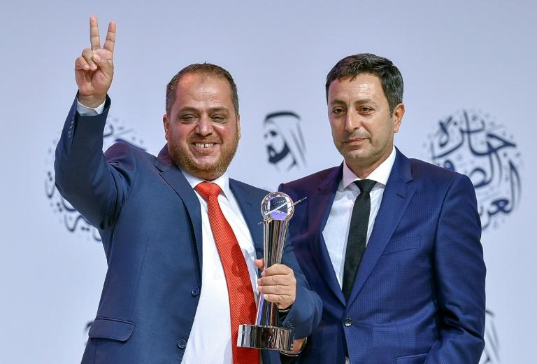 AFP photographer Jaafar Ashtiyeh (L) gestures after receiving a top Arab prize for his coverage of the clashes in Kfar Qaddum at the 16th Arab Journalism Award (AJA) in Dubai's Madinat Jumeirah on May 2, 2017