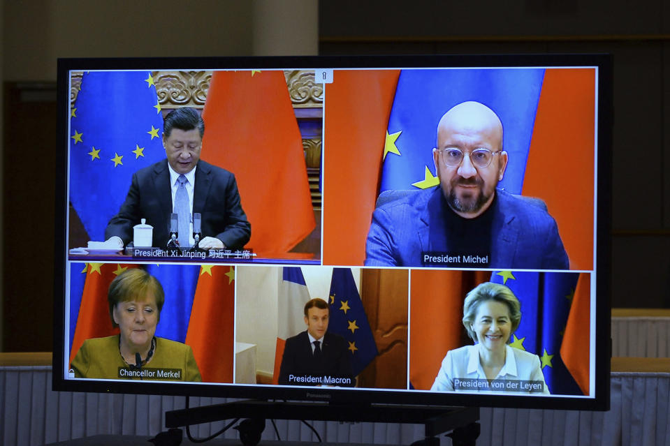 A screen displays live Chinese President Xi Jinping, top left, European Council President Charles Michel, top right, European Commission President Ursula von der Leyen, bottom right, French President Emmanuel Macron, bottom center, and German Chancellor Angela Merkel during an EU-China Leaders' meeting video conference at the European Council headquarters in Brussels, Wednesday, Dec. 30, 2020. The European Union top officials and China president Xi Jinping will conclude Wednesday a business investment deal that will open big opportunities to European companies, with the potential to irk the new American administration. (Johanna Geron, Pool Photo via AP)