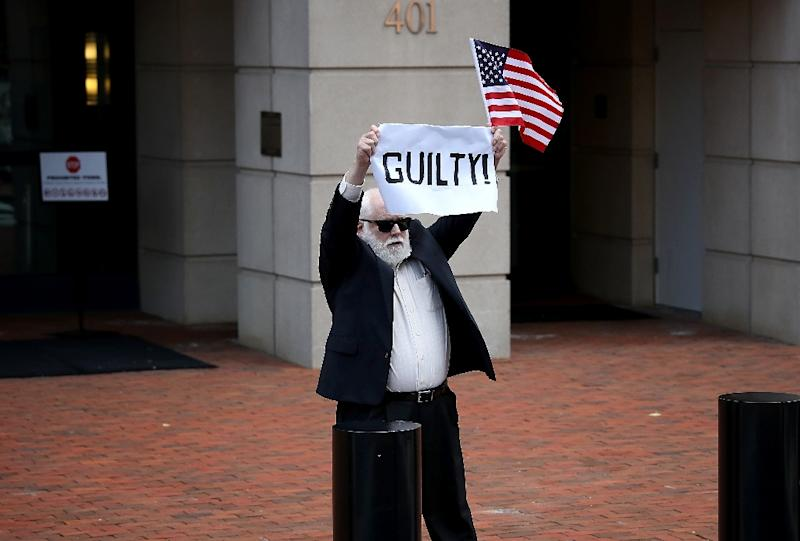 A lone protester holds up a sign and an American flag outside the Alexandria courthouse after former Trump campaign chairman Paul Manafort was found guilty of tax crimes and bank fraud (AFP Photo/WIN MCNAMEE)