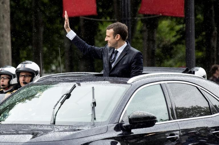 French President Emmanuel Macron waves as he parades under the rain in a Citroen DS car on the Champs Elysees avenue, after his formal inauguration ceremony in 2017