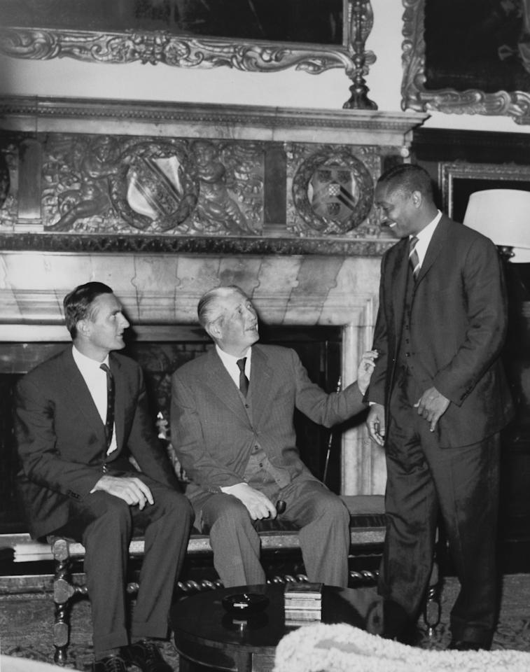 British Prime Minister Harold Macmillan (1894 - 1986) invites West Indian Test cricket captain Frank Worrell (right) to sit next to him for a photograph at Chequers in Buckinghamshire, 11th September 1963. On the left is England captain Ted Dexter. Both team captains have been invited to Chequers for lunch as guests of the PM. (Photo by Central Press/Hulton Archive/Getty Images)