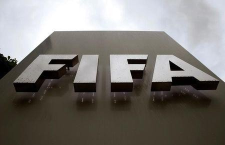 Raindrops flow down on a logo in front of FIFA's headquarters in Zurich
