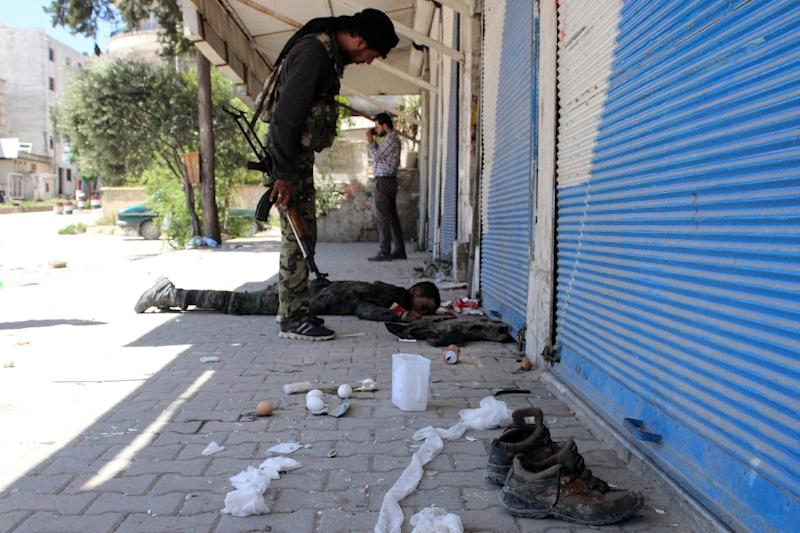 An armed rebel fighter inspects a body, reportedly belonging to Syrian government forces, on April 26, 2015 in the northern town of Jisr al-Shughur (AFP Photo/Ali Nasser)