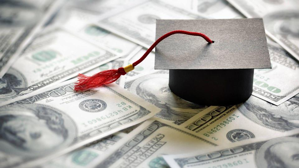 Graduation mortar board cap on one hundred dollar bills concept for the cost of a college and university education.