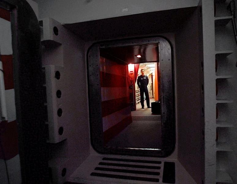 "FILE - This April 15, 1997 file photo shows an Air Force missile crew commander standing at the door of his launch capsule 100-feet under ground where he and his partner are responsible for 10 nuclear-armed ICBM's, in north-central Colorado. Twice this year alone, Air Force officers entrusted with the launch keys to nuclear-tipped missiles have been caught leaving open a blast door meant to help prevent a terrorist or other intruder from entering their underground command post and potentially compromising secret launch codes, Air Force officials told The Associated Press. The missiles stand in reinforced concrete silos and are linked to the control center by buried communications cables. The ICBMs are split evenly among ""wings"" based in North Dakota, Wyoming and Montana. Each wing is divided into three squadrons, each responsible for 50 missiles. (AP Photo/Eric Draper, File)"
