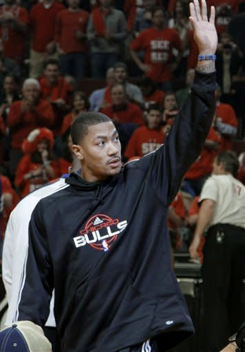 Injured Chicago Bulls star Derrick Rose acknowledges the crowd after bringing out the game ball before Game 2 of an NBA basketball first-round playoff series against the Philadelphia 76ers, in Chicago on Tuesday, May 1, 2012. The 76ers won 109-92 to even the series at a game apiece. (AP Photo/Daily Herald, Steve Lundy) MANDATORY CREDIT TV OUT MAGS OUT