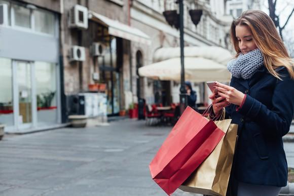 A woman in a winter coat holds shopping bags.