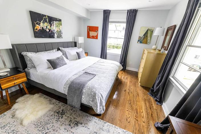 A bedroom at 510 Queens Road features art by Charlotte's Arthur Brouthers over the bed.