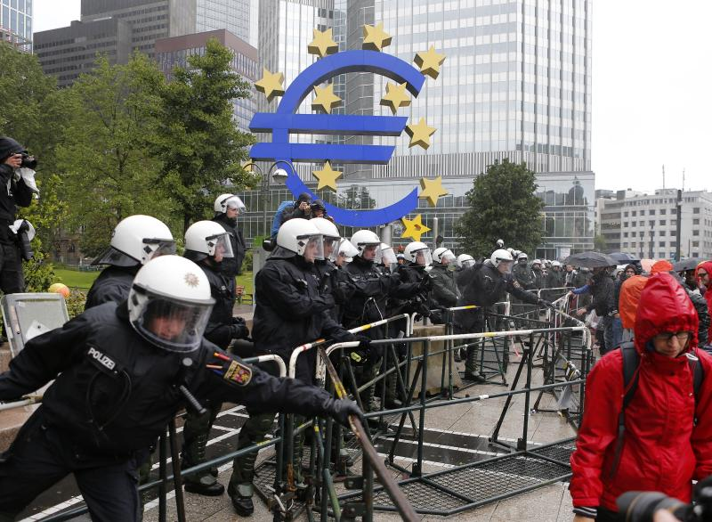 German police officers stand behind metal barricades during a demonstration of some hundred anti-capitalism Blockupy protesters in front of the European Central Bank in Frankfurt, Friday, May 31, 2013. Members of the Blockupy group say they will try to prevent employees from reaching the ECB building for several hours Friday to highlight what they say is the bank's role in enforcing the harsh spending cuts introduced to tackle the euro area's three-year debt crisis. (AP Photo/Michael Probst)