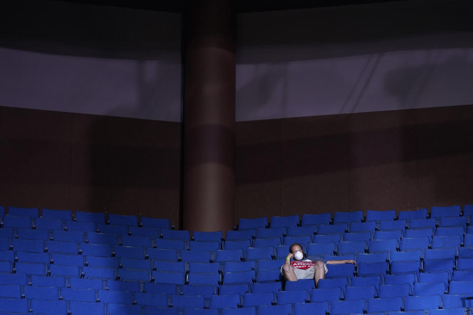 FILE - In this June 20, 2020, file photo, a supporter of President Donald Trump sits in the stands wearing a face mask during a campaign rally at the BOK Center in Tulsa, Okla. (AP Photo/Evan Vucci, File)