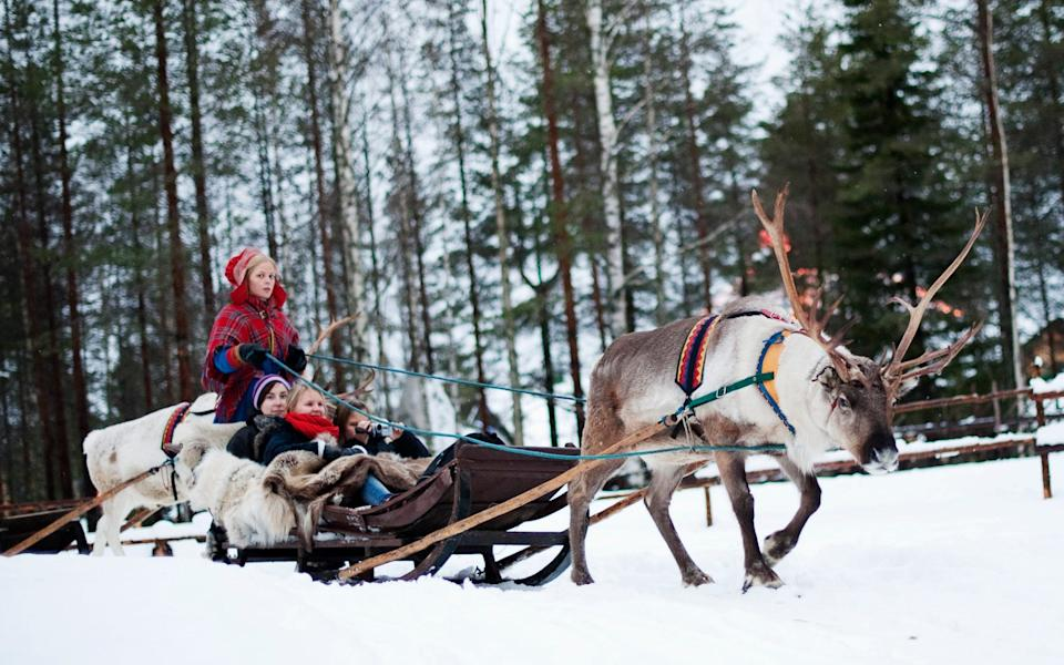 "A woman in traditional Laplander costume rides with a group of tourists on a reindeer sled in the ""Santa Claus Village"" near Rovaniemi - JONATHAN NACKSTRAND/AFP via Getty Images"