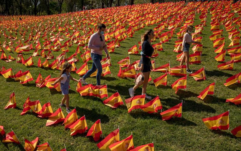Madrid, Spain: People walk across Spanish flags placed at Roma Park to honour the country's coronavirus dead during the second wave of the Covid pandemic - Getty Images