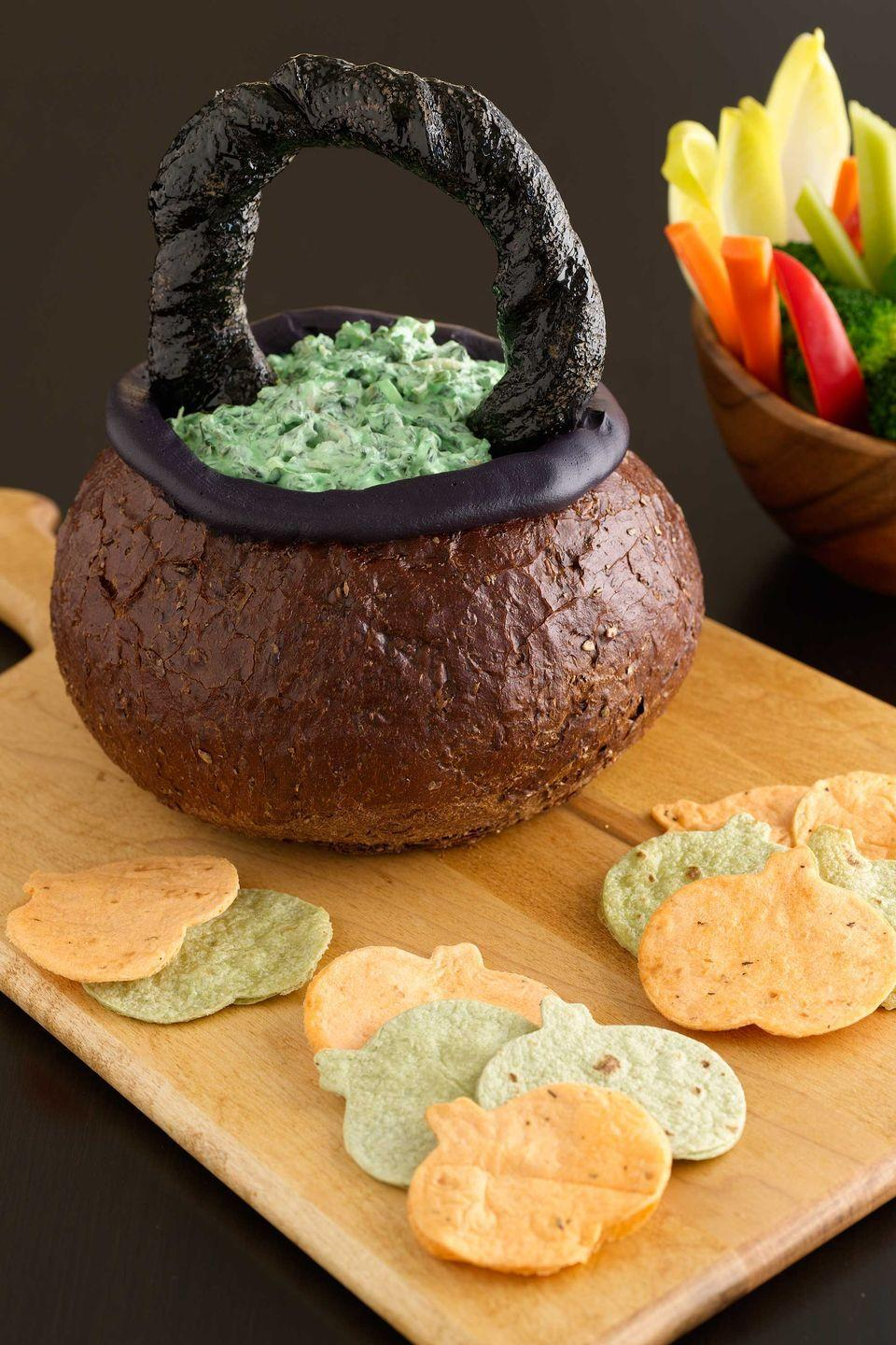 """<p>Impress guests with this crafty Halloween appetizer. It cleverly transforms pumpernickel bread, breadsticks, and cream cheese into a basket, before filling it with a super-simple creamy spinach dip.</p><p><a href=""""https://www.womansday.com/food-recipes/food-drinks/recipes/a10930/spooky-spinach-dip-in-bread-bowl-cauldron-recipe-122179/"""" rel=""""nofollow noopener"""" target=""""_blank"""" data-ylk=""""slk:Get the Spinach Dip in a Bread Bowl Cauldron recipe."""" class=""""link rapid-noclick-resp""""><em>Get the Spinach Dip in a Bread Bowl Cauldron recipe.</em></a> </p>"""