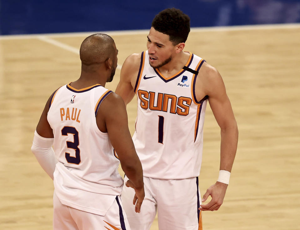 Chris Paul, left, of the Phoenix Suns celebrates his 3-point shot with teammate Devin Booker, right, in the fourth quarter of an NBA basketball game Monday, April 26, 2021, in New York. (Elsa/Pool Photo via AP)