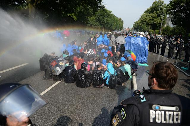 <p>Police uses a water canon while demonstrators block a street during protests against the G-20 summit in Hamburg, Germany, Friday, July 7, 2017. (Daniel Reinhardt/dpa via AP) </p>