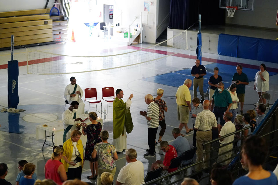 Father David Ducote leads Mass in the gymnasium at St. Joan of Arc Catholic Church in LaPlace, La., in the aftermath of Hurricane Ida, Sunday, Sept. 5, 2021. (AP Photo/Matt Slocum)