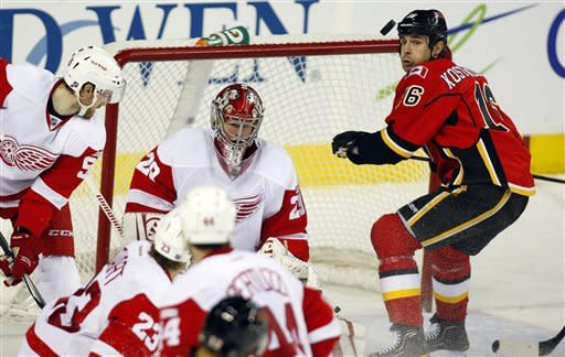 Detroit Red Wings goalie Ty Conklin, center, loses sight of the puck as Calgary Flames' Tom Kostopoulos looks for a rebound during the second period of an NHL hockey game in Calgary, Alberta, Thursday, Dec. 22, 2011. (AP Photo/The Canadian Press, Jeff McIntosh)