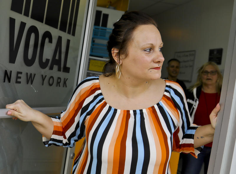 In this Friday March 15, 2019 photo, Laura Levine looks out from the doorway of Vocal NY, an organization that works with addicts where she is the health educator and coordinator for the opioid reversal drug Narcan, in the Brooklyn borough of New York. New York state is considering providing medication-assisted treatment to all prison and jail inmates struggling with opioid addiction. (AP Photo/Bebeto Matthews)