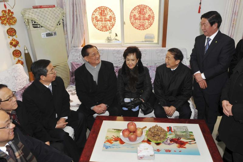In this photo provided by China's Xinhua News Agency, Taiwan's Kuomintang Honorary Chairman Lien Chan, center left, visits the home of a villager at Guajiayu Village on the outskirts of Beijing, China, Tuesday, Feb. 18, 2014. Lien, also chairman of a foundation on cross-strait peaceful development, is leading a delegation from Taiwan for a four-day visit to China. (AP Photo/Xinhua, Chen Yehua) NO SALES