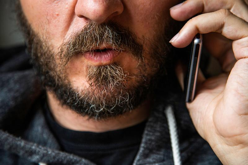 Close up portrait of bearded man talking on smart phone, focus on lips, no eyes, secret talk, criminal threating someone