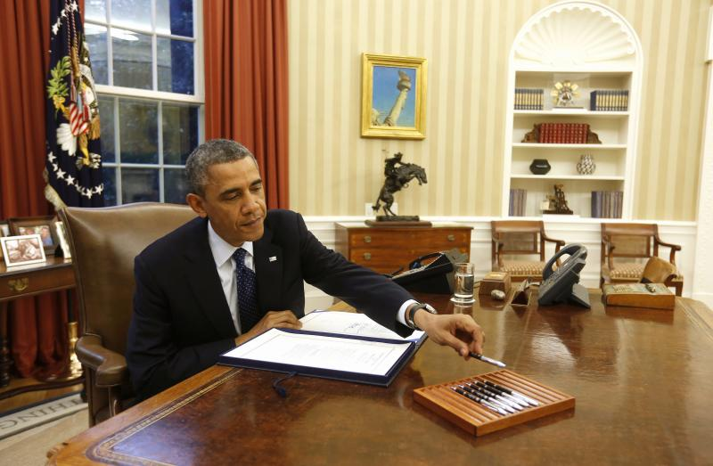 U.S. President Obama reaches for a pen as he signs a bill in the Oval Office of the White House in Washington