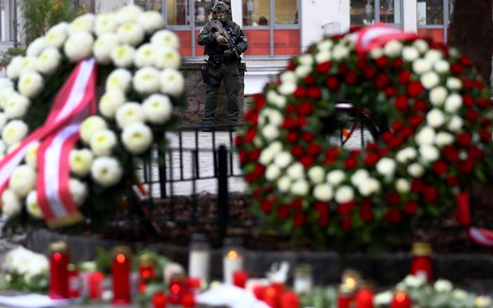 An military police officer guard at the crime scene behind wreaths and candles in Vienna, Austria, Wednesday, Nov. 4, 2020. Several shots were fired shortly after 8 p.m. local time on Monday, Nov. 2, in a lively street in the city center of Vienna. (AP Photo/Matthias Schrader) - Matthias Schrader/AP