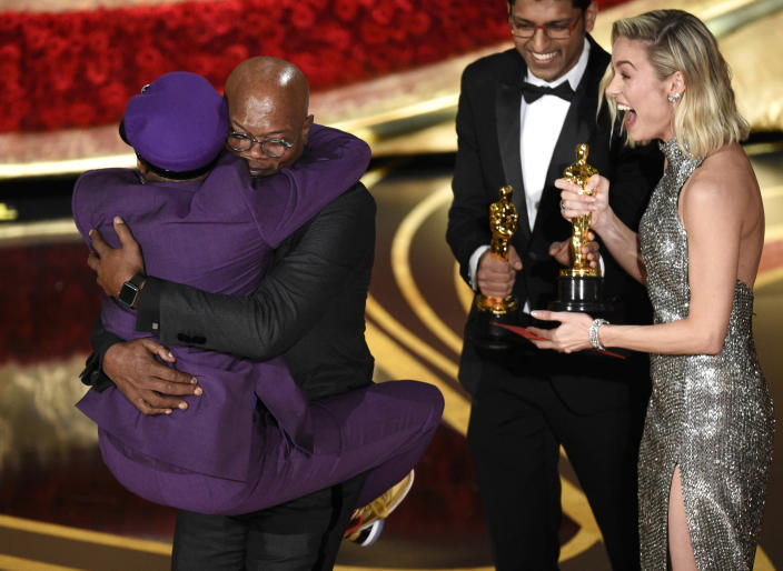 """Spike Lee, winner of the award for best adapted screenplay for """"BlacKkKlansman"""" jumps into the arms of presenter Samuel L. Jackson as fellow presenter Brie Larson, right, looks on, at the Oscars in Los Angeles on Feb. 24, 2019. It was the first Oscar awarded to the veteran filmmaker. (Photo by Chris Pizzello/Invision/AP)"""
