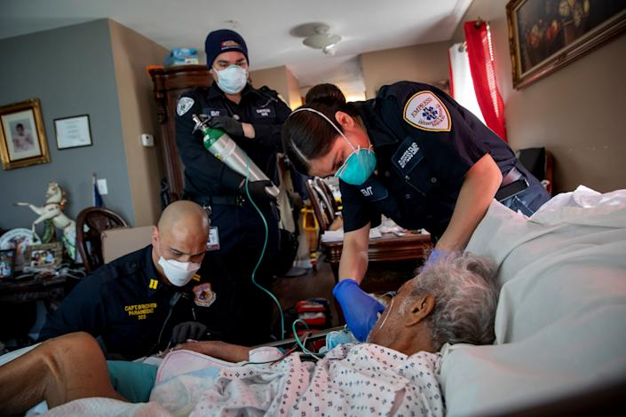 Image: Medics prepare to intubate a patient showing COVID-19 symptoms at his home in Yonkers, N.Y., on April 6, 2020. (John Moore / Getty Images file)