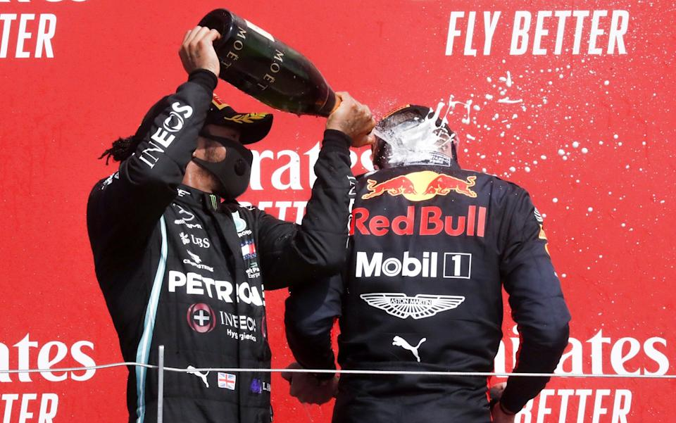 Winner Dutch Formula One driver Max Verstappen of Aston Martin Red Bull Racing (R) and second British Formula One driver Lewis Hamilton of Mercedes-AMG Petronas (L) celebrate on the podium after the 70th Anniversary Formula One Grand Prix of Great Britain at the Silverstone Circuit - SHUTTERSTOCK