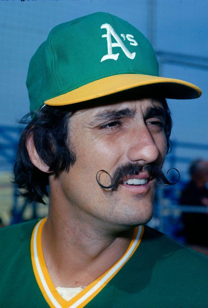 """<p><strong>Rollie Fingers</strong></p><p>At one point, the handlebar mustache was basically a must for any mustachioed dude. Nowadays, it's a riskier look mostly favored by professional facial hair competitors and hipster bartenders who make their own """"creative"""" bitters. But if you're going to try a mustache, why not go all in. To get a handlebar, keep the middle point (under your nose) trimmed and let the corners grow long. Then, use a strong <a href=""""https://www.amazon.com/Fisticuffs-Strong-Hold-Mustache-Wax/dp/B00W41AOFE/ref=sr_1_1_sspa?crid=3DUGDHK5Z04W0&dchild=1&keywords=mustache+wax&qid=1595442061&sprefix=mustache+wax%2Caps%2C1105&sr=8-1-spons&psc=1&spLa=ZW5jcnlwdGVkUXVhbGlmaWVyPUFBRUFEN0lUSEVaTDMmZW5jcnlwdGVkSWQ9QTA3NTI1NzEzVllBVkEzRVA4SVNCJmVuY3J5cHRlZEFkSWQ9QTA5OTEzNDZLMlVaNTRFTjJMMVcmd2lkZ2V0TmFtZT1zcF9hdGYmYWN0aW9uPWNsaWNrUmVkaXJlY3QmZG9Ob3RMb2dDbGljaz10cnVl&tag=syn-yahoo-20&ascsubtag=%5Bartid%7C2139.g.33501753%5Bsrc%7Cyahoo-us"""" rel=""""nofollow noopener"""" target=""""_blank"""" data-ylk=""""slk:mustache wax"""" class=""""link rapid-noclick-resp"""">mustache wax</a> or balm to twirl the ends and keep them stiff.</p>"""