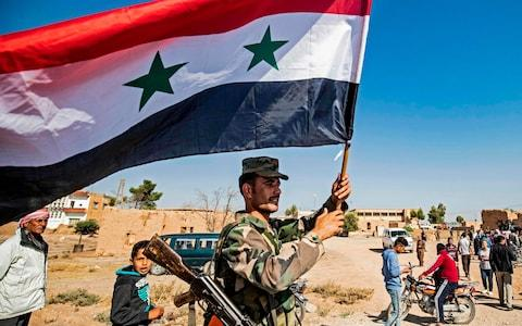 A Syrian regime soldier waves the national flag a street on the western entrance of the town of Tal Tamr in the countryside of Syria's northeastern Hasakeh province on October 14, 2019 - Credit: AFP