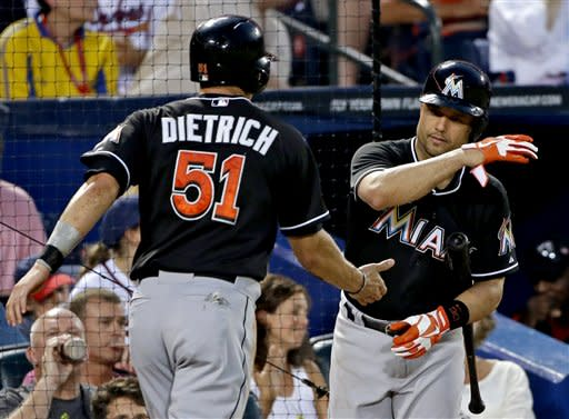 Miami Marlins' Derek Dietrich, left, is high-fived by teammate Placido Polanco after Dietrich scored off a single by Greg Dobbs in the sixth inning of a baseball game against the Atlanta Braves, Tuesday, July 2, 2013, in Atlanta. (AP Photo/David Goldman)