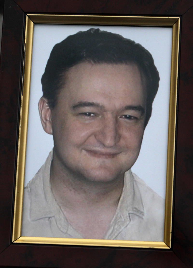 FILE - This Monday, Nov. 30, 2009 file photo shows a portrait of lawyer Sergei Magnitsky who died in jail, which is held by his mother Nataliya Magnitskaya, unseen, as she speaks during an  interview with The Associated Press in Moscow. Russia is preparing to put lawyer Sergei Magnitsky on trial, even though he is dead, in the latest twist in a case that has severely strained U.S.- Russian relations. Magnitsky, a lawyer for the Hermitage Capital fund, died in jail in 2009 after accusing Russian officials of colluding in stealing $230 million from the state. He was arrested on suspicion of tax evasion by the same Interior Ministry officials he accused. A Moscow court on Monday Jan. 28, 2012 set preliminary hearings in the posthumous trial for Feb. 18. (AP Photo/Alexander Zemlianichenko, File)