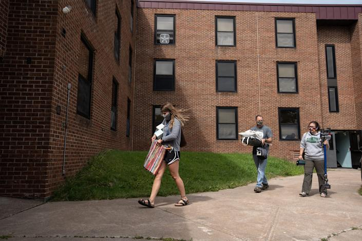 Lake Superior State University junior Rebecca Weipert carries her items with the help of her father William Weipert and mother Heidi Weipert at Osborn Hall during a move-in day for students at Lake Superior State University in Sault Ste. Marie.