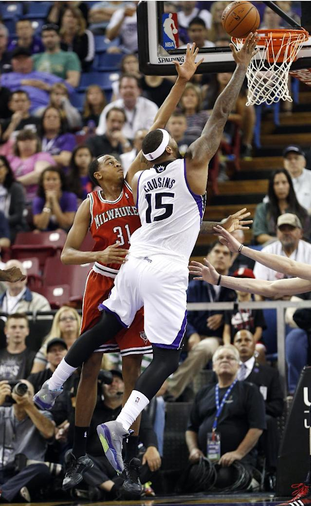 Sacramento Kings center DeMarcus Cousins, right, drives to the basket past Milwaukee Bucks center John Henson during the first quarter of an NBA basketball game in Sacramento, Calif., Sunday, March 23, 2014. (AP Photo/Rich Pedroncelli)