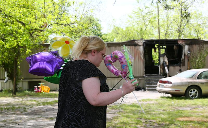 Jessica Long brings balloons to leave in front of a mobile home where four children were killed in a fire the day before in Hartsville, S.C., Thursday, April 25, 2013. Authorities say smoke inhalation killed 10-month-old twin sisters Myasia and Kynasia Hawkins and their brothers, 2-year-old Camaron Mason and 4-year-old Delonta Dixon. Hawkins daughter is the children's mother. (AP Photo/The Morning News, Gavin Jackson) LOCAL TV OUT